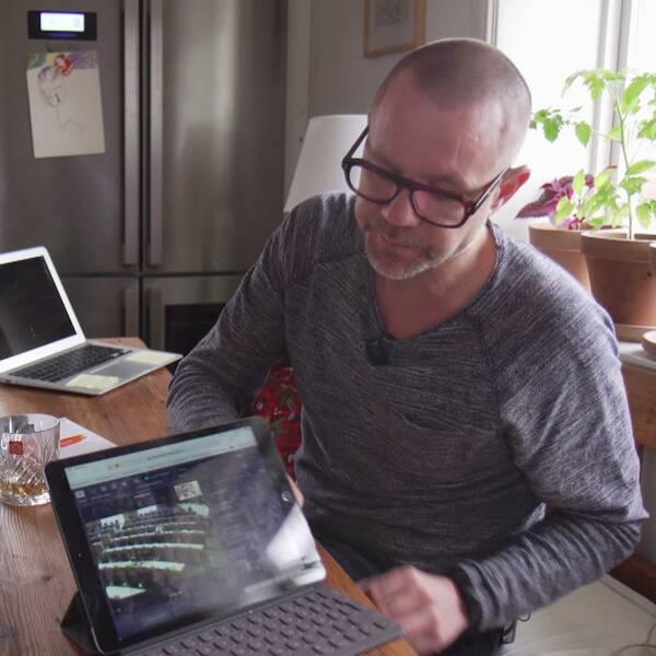 en man sitter vid köksbord med laptop, bild från EU-parlamentet syns på skärmen
