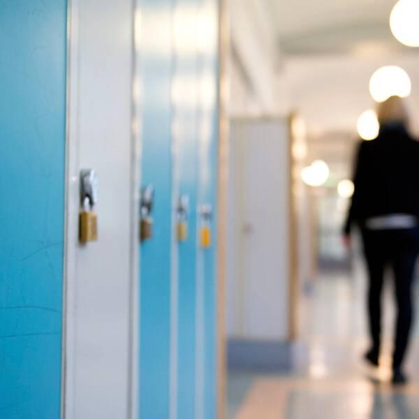 elev går i korridor med skåp med hänglås