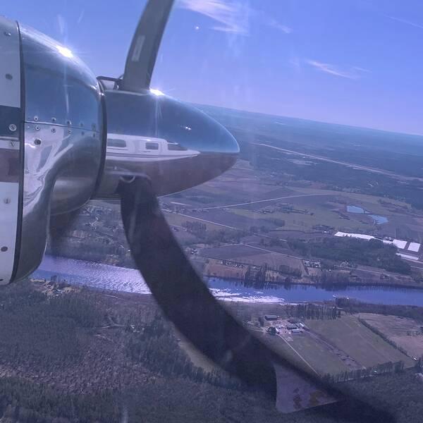 flygbild över jordbruks- och skogsmark, en flygplanspropeller i förgrunden