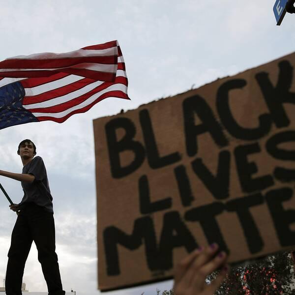 """Ung man vajar USA:s flagga. En skylt med texten """"Black lives matter"""" syns också."""