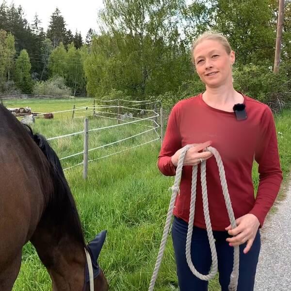 Annelie Manberger står på en väg med häst i grimskaft. Det är sommar och gröna hagar syns i bakgrunden.