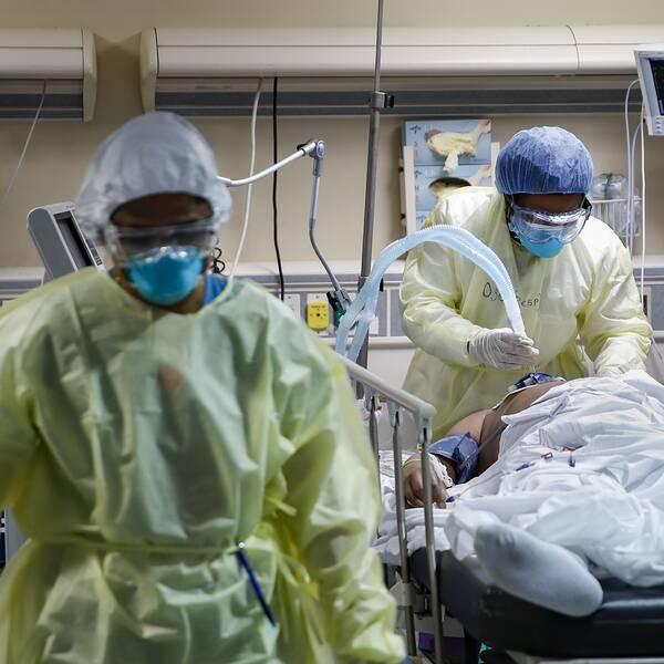 Två vårdarbetare i full skyddsmundering hjälper en patient som ligger på en brits.