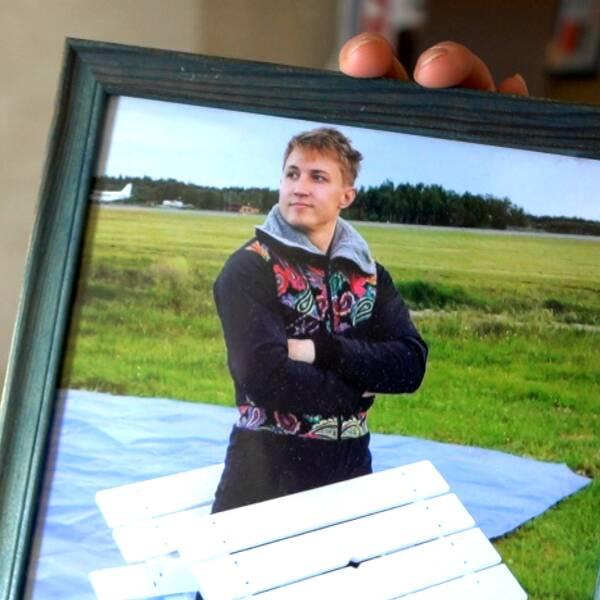 Ett sorgset par sitter med gråten i halsen i sommarmiljö, till höger en bild på sonen som omkom för ett år sedan