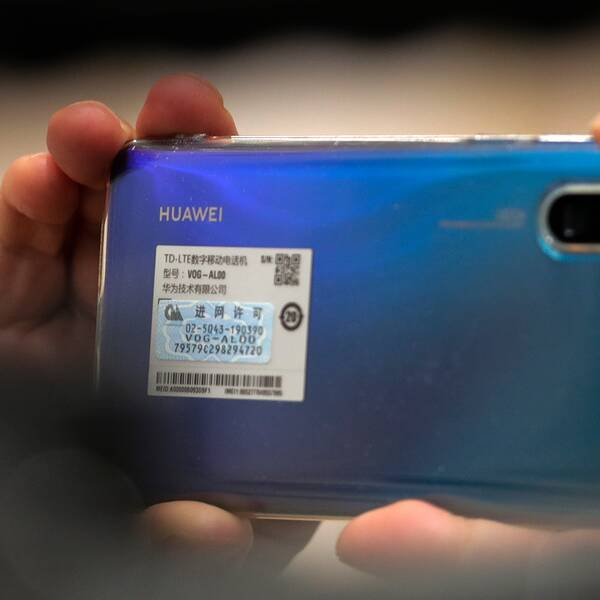 En person håller upp en blå Huawei-mobil.