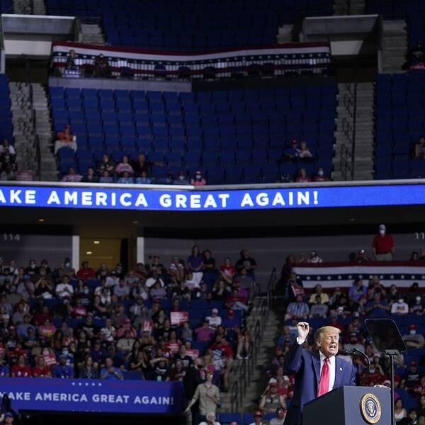 Donald Trump står vid talarstolen på scenen i en stor arena med halvtomma läktare.