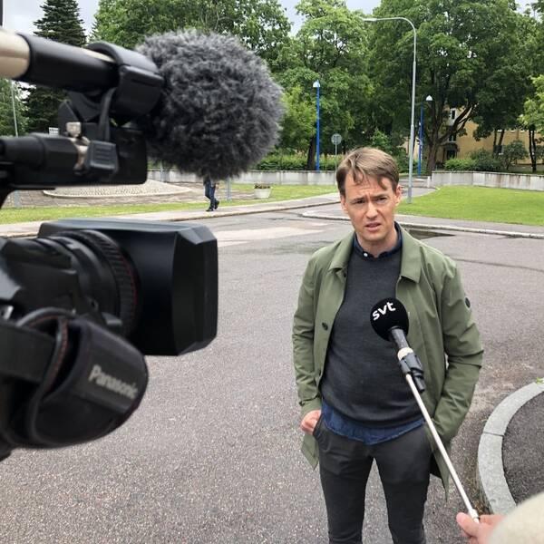 en man intervjuas utomhus, i förgrunden SVT:s filmkamera och mikrofon på pinne för att hålla avstånd