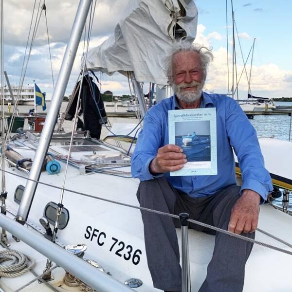 en skäggig man sitter på en segelbåt