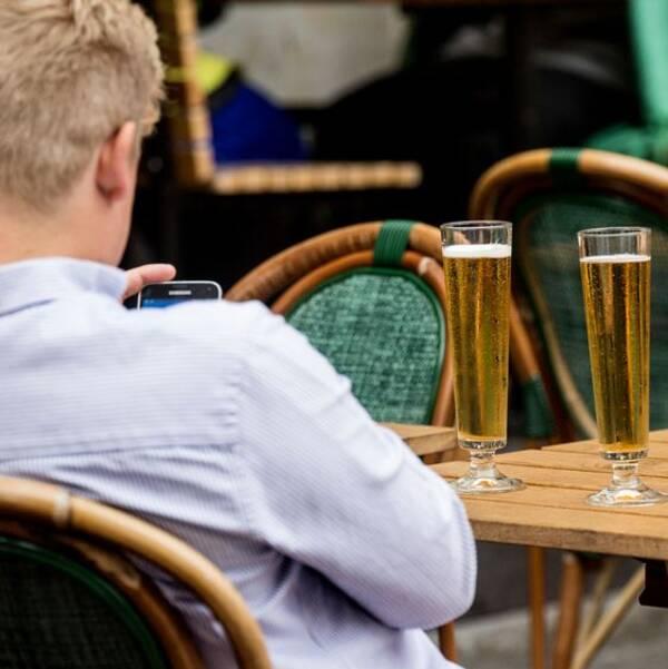 En man i blå skjorta sitter med sin telefon i handen på en uteservering.