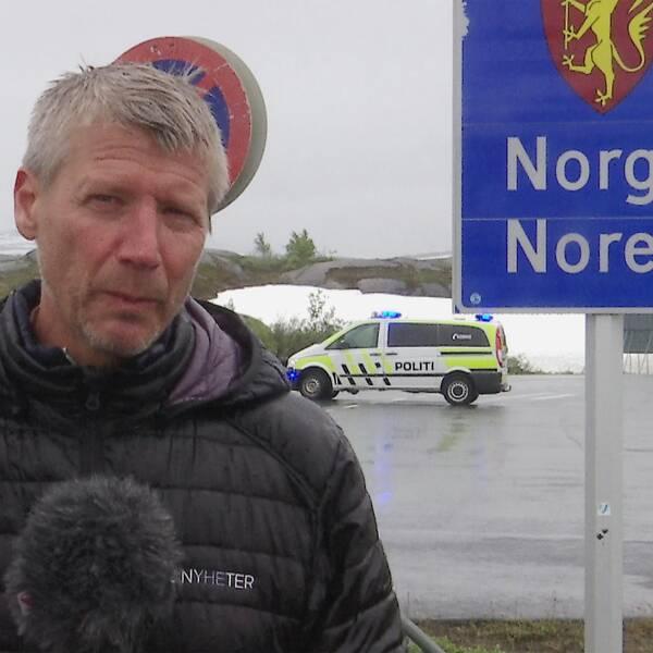 Reportern står vid gränsen till Norge. Hans står bredvid gränsskylten till Norge och i bakgrunden syns en norsk polisbil.