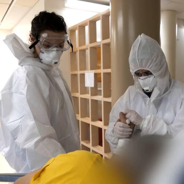 Sjukvårdspersonal med andningsskydd och skyddskläder.