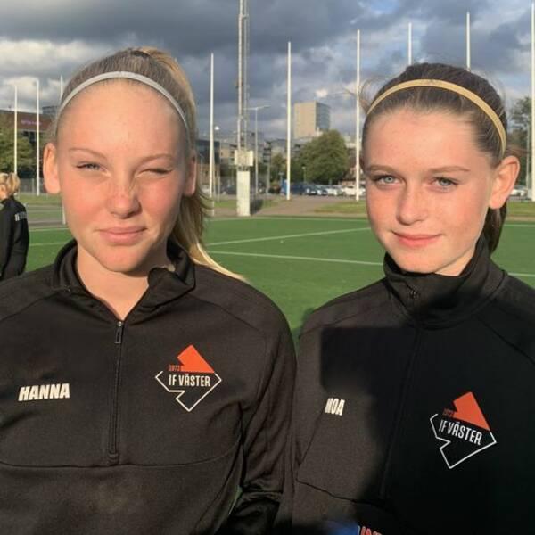 Två flickor med svarta träningströjor och pannband på en fotbollsplan.