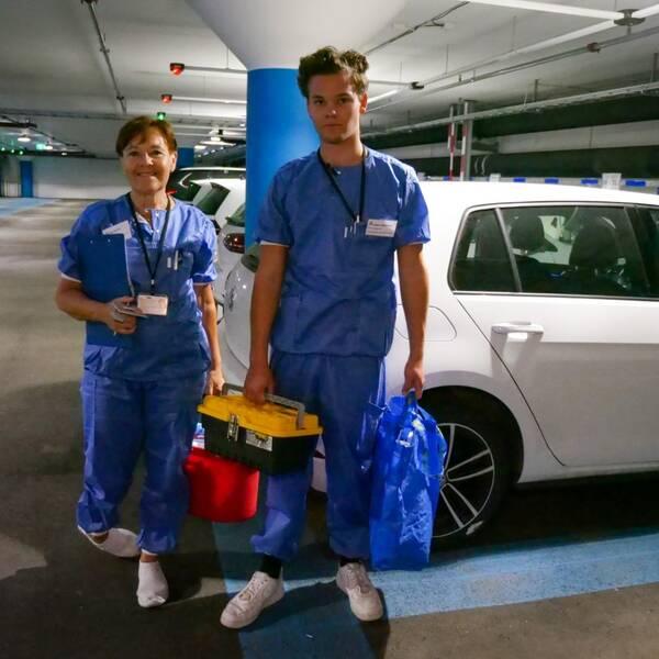 Två personer i blåa skyddskläder står i ett bilgarage