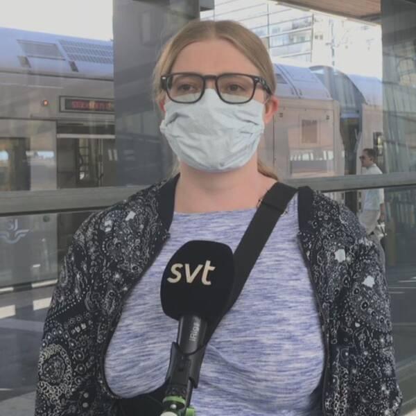Ett SJ-tåg till vänster i bild och till höger är Sofia Lindström, en Uppsalapendlare som bär munskydd.