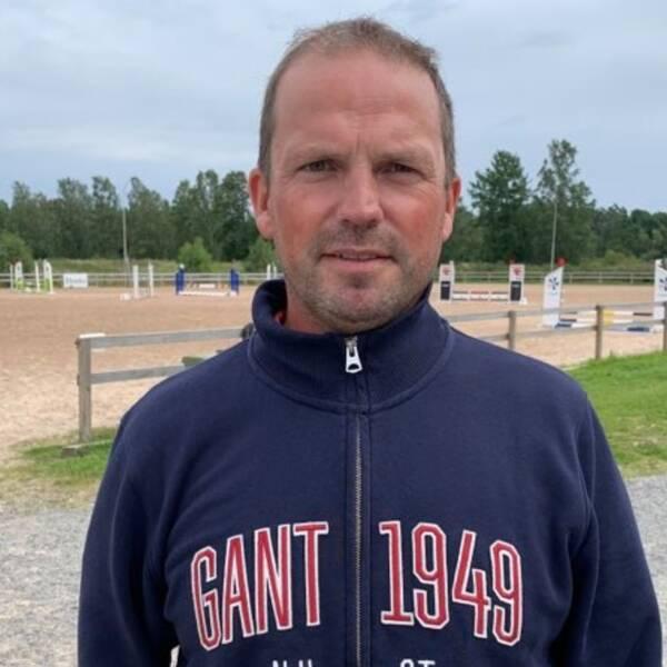 Tobias Jönberg, ordförande Växjöortens Fältrittklubb står i en blå jacka framför en hoppbana.