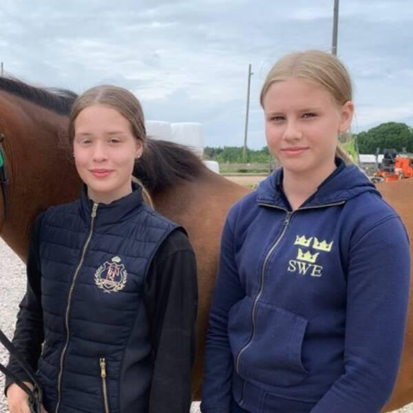 Två unga tjejer står med ridkläder på och håller i en häst