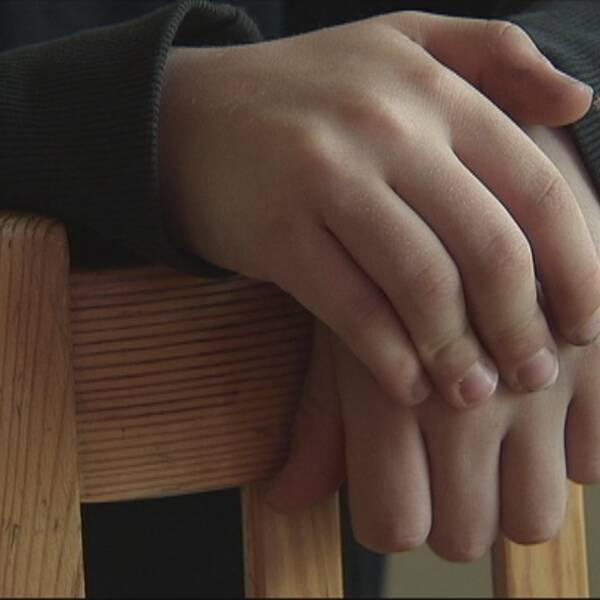 Ett barn lutar sig över en brun trästol, i bilden syns händerna