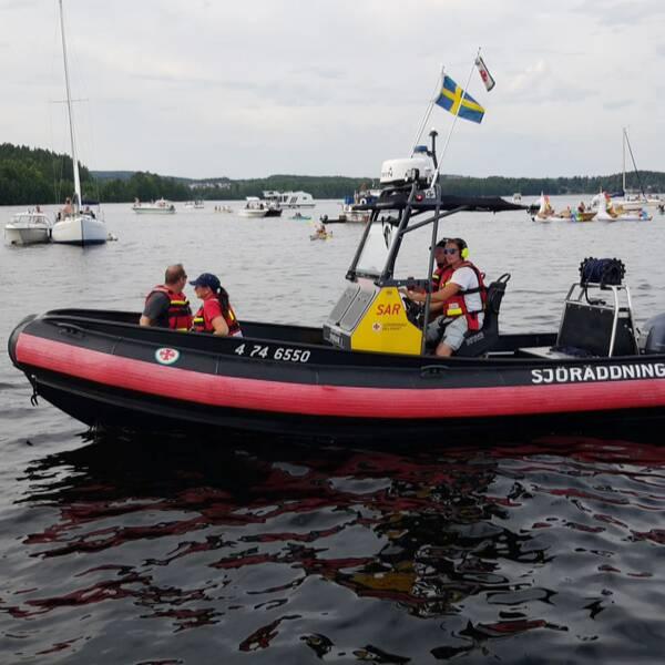 delad bild: Hundratals båtar som samlats på sjön Runn, samt en av Sjöräddningssällskapets båtar.
