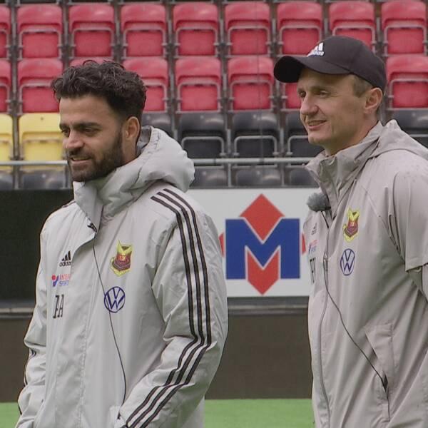 Två fotbollstränare som står på fotbollsplanen intill varandra och övervakar en träning med ÖFK