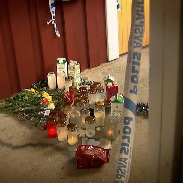 Ljus, blommor och mjölkförpackningar står utanför en lägenhetsdörr, avspärrningsband från polisen syns