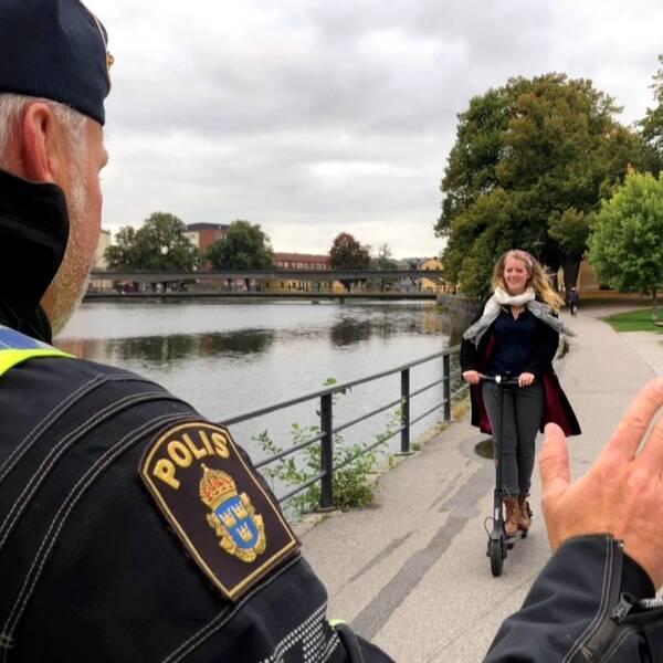 Reportern Otilia Bogen håller i en elsparkcykel och trafikpolisen Tomas Bonn inspekterar den. I bakgrunden syns Eskilstunaån och delar av Gamla stan/Söder.