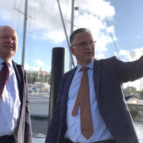 Torkild Strandberg (L) och stadsdirektör Christian Alexandersson vid hamn i Landskrona och Christian Alexandersson pekar ut förbi kameran.