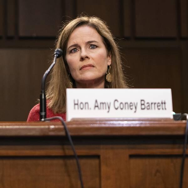 Bild tagen underifrån. Domarkandidaten Amy Coney Barrett sitter framför sin mikrofon i USA:s senat.