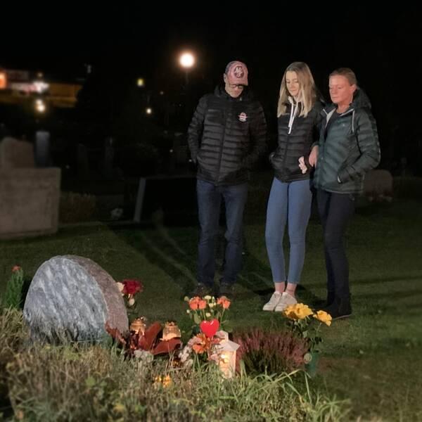 tre personer vid en gravsten, mörk kväll
