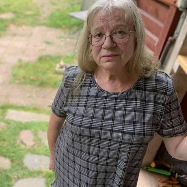 Lisbet Tengelin står på trappavsatsen ut från huset där hennes make trillade när han försökte krypa ut till ambulansen.