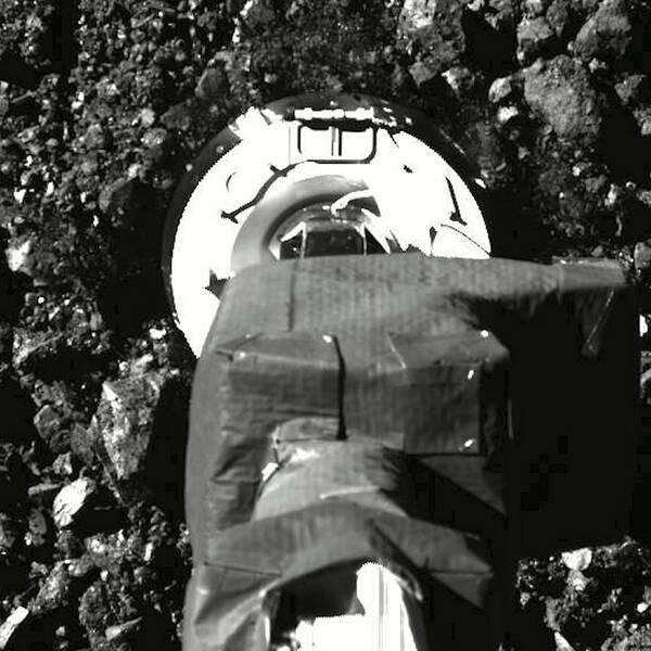 En svartvit bild på rymdsondens fot då den landat på asteroiden Bennu.