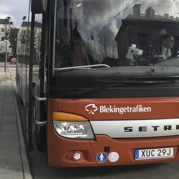 Till vänster röd buss tillhörande Blekingetrafiken stillaståendes på hållplats. Till höger Peter Christensen ståendes utomhus med en busshållplats ur fokus i bakgrunden.