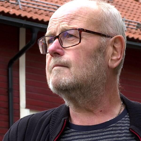 En man med glasögon blickar bortåt