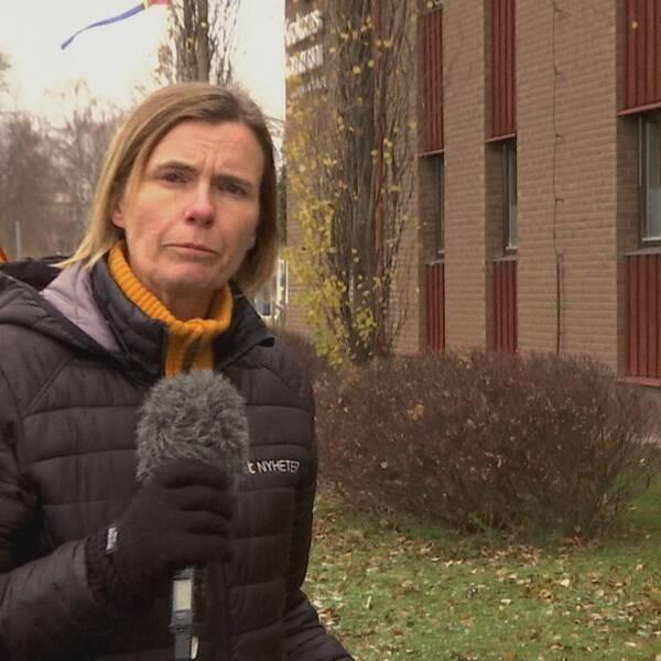 Reporter Sara Leijman står utomhus, iklädd svart jacka, och pratar i mikrofonen framför kameran.