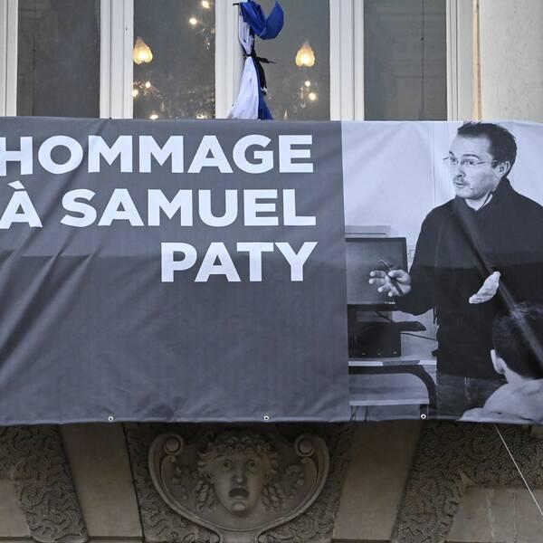 Bilden visar en demonstration i Frankrike till stöd för yttrandefriheten efter mordet på läraren Samuel Paty, vars bild syns på en banderoll.