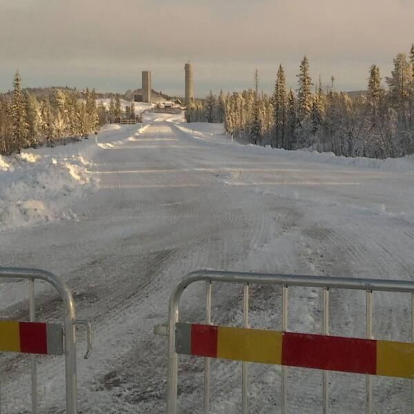 vinterväg med skog på sidorna, avspärrning i förgrund, industribyggnader syns längre bort