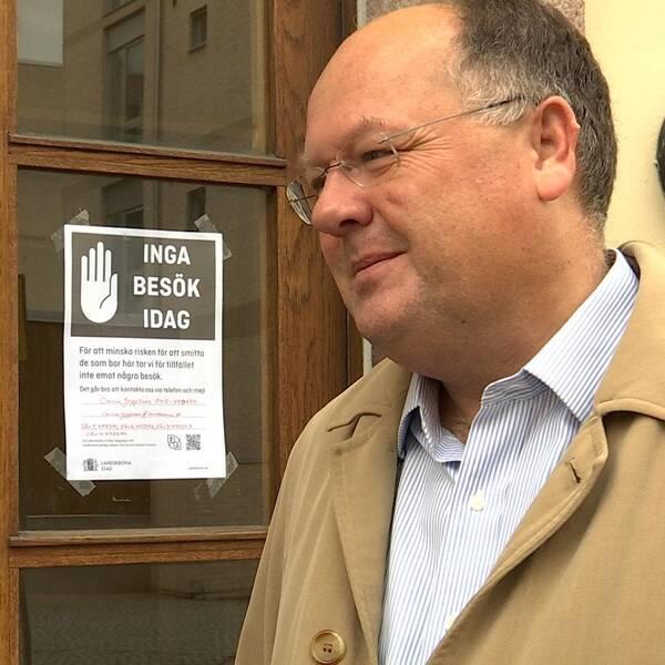 """Torkild Strandberg bredvid en skylt på dörren till ett äldreboende. Där står """"INGA BESÖK IDAG""""."""