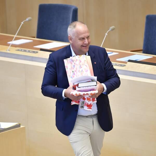 Vänsterpartiets partiledare Jonas Sjöstedt (V) med sina avtackningspresenter vid riksdagsårets första partiledardebatt i riksdagen.
