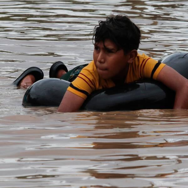 Bilden v isar kvinnor och män som försöker rädda sina ägodelar i staden El Progreso i Honduras. I samhället Planeta försöker ett barn ta sig över en översvämmad gata.