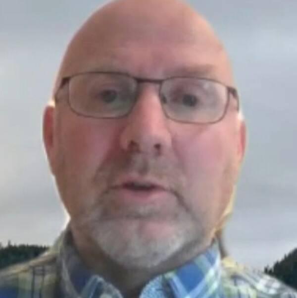 Dubbelbild. Till vänster skallig man med grått skägg och glasögon, mannen har blåvitgrön rutig skjorta. Till höger fasad av hus i gult tegel med texten Ragunda.