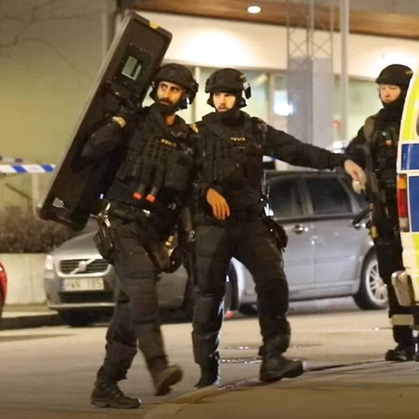 Fyra poliser i hjälmar, en med sköld, framför en polisbuss.