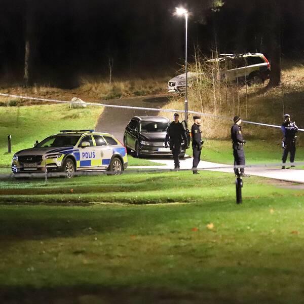 Flera poliser och poisbilar står vid en avspärrning i ett grönområde.