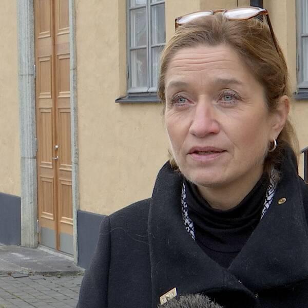 KVinna med långt brunt uppsatt hår och glasögon på huvudet står framför ett gulrappat hus och intervjuas. Kvinan har en mörk rock på sig.