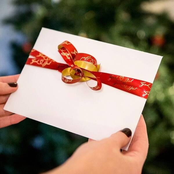 Bild på två händer som håller i ett vitt kuvert med ett rött presentsnöre på. I bakgrunden en suddig julgran.
