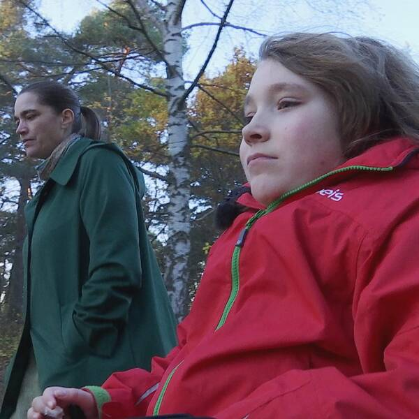 Susanne och Edvin går på en gångväg i skogen. Edvin kör rullstol.