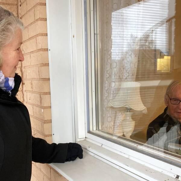 Gunvor Åberg står utanför ett fönster och tittar in i en lägenhet där hennes man Palle Åberg sitter.