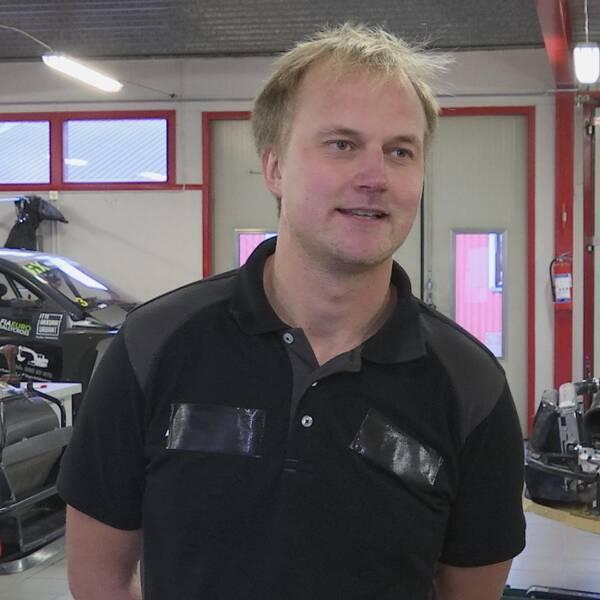Joel Christoffersson i sitt garage med rallycrossbilar i bakgrunden.