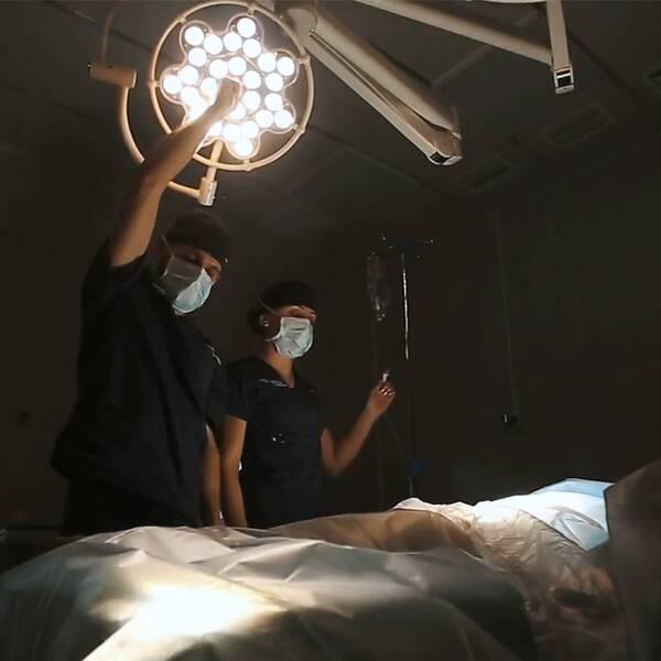 Sjukhuspersonal står vid ett operationsbord