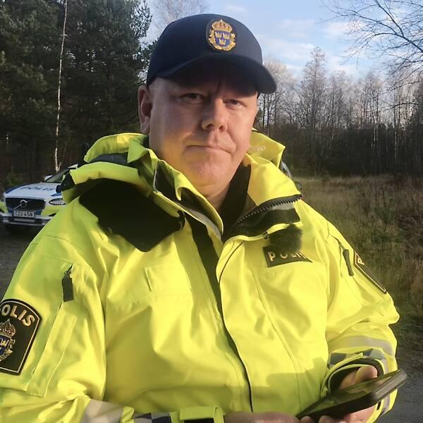 Tobias har på sig en signalgul polisjacka och keps. I handen håller han sin telefon och i bakgrunden skymtar en polisbil och lite skog.