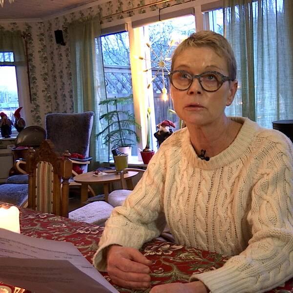 Elisabeth läser ur ett papper. Hon sitter vid ett bord i sitt vardagsrum med julpynt i fönstret bakom.