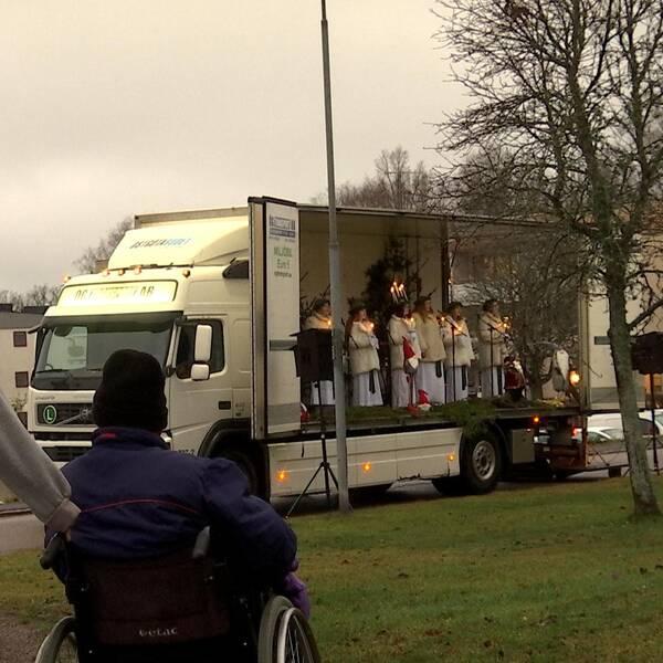 På flaket på en lastbil står ett luciatåg och en bit bort sitter man i rullstol och en vårdklädd kvinna står bredvid.