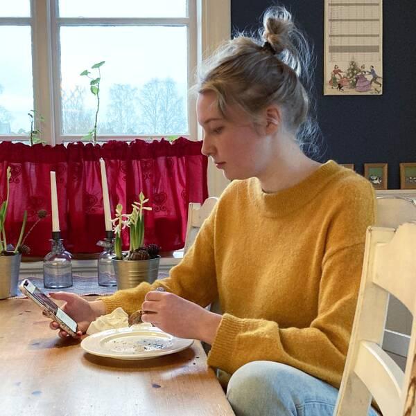 Mira Åslin äter en smörgås och tittar på sin mobiltelefon.